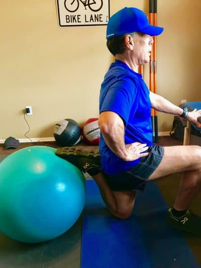 Rivak Hoffman Scottsdale Personal Trainer performing kneeling Rectus Femoris stretch to resolve lower back pain