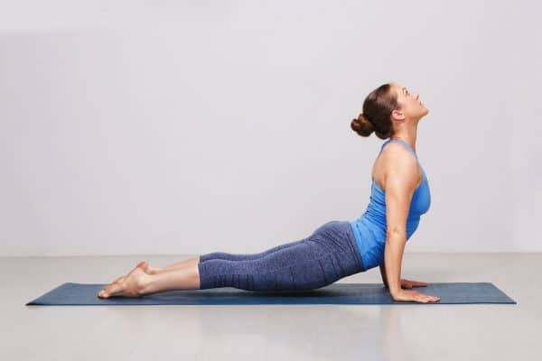 Athletic woman doing the McKenzie Press up to resolve lower back pain.